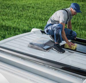 men-cleaning-camper-van-rv-roof-installed-solar-pa-CLNX5X8